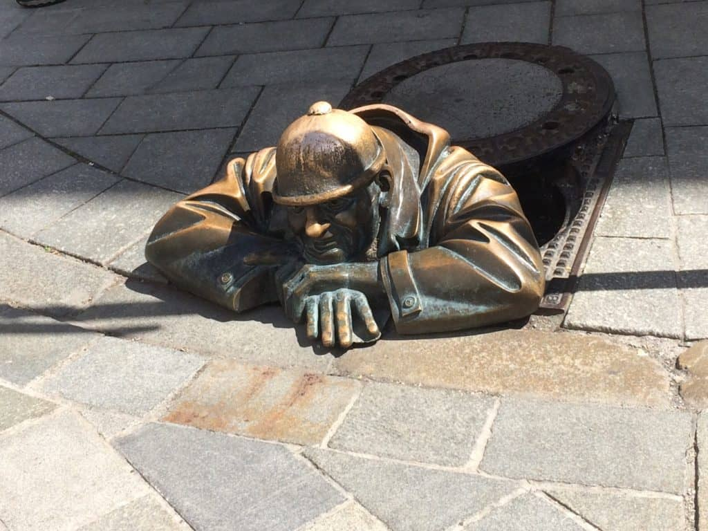 Life size bronze statue of a man crawling out from a grid on the street in Bratislava